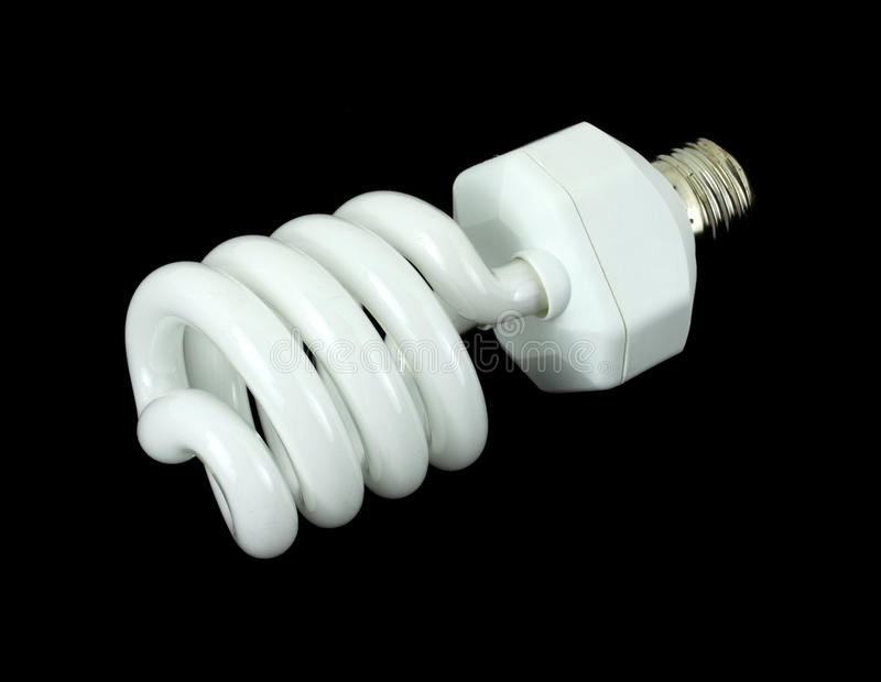 Spiral compact fluorescent light bulb. A compact fluorescent light bulb against a black background royalty free stock images
