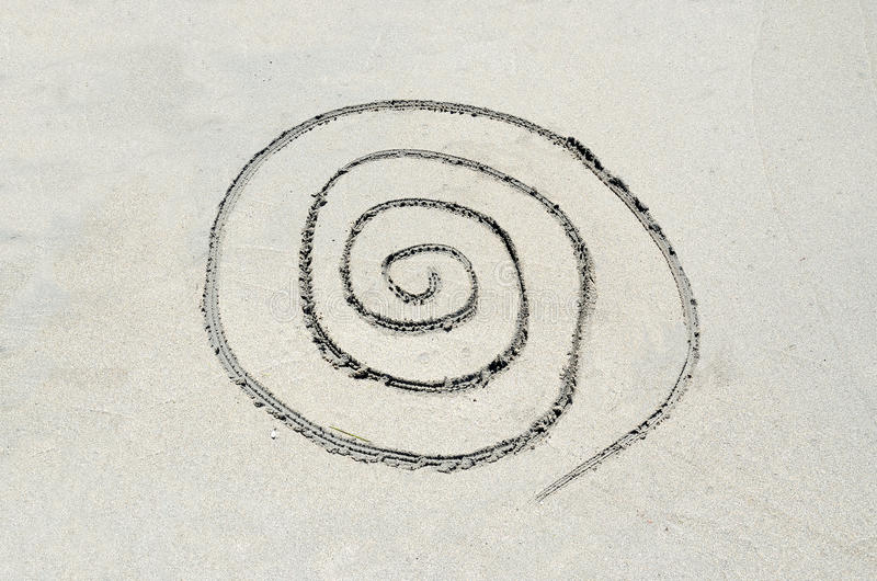 Spiral drawn in sand royalty free stock photography
