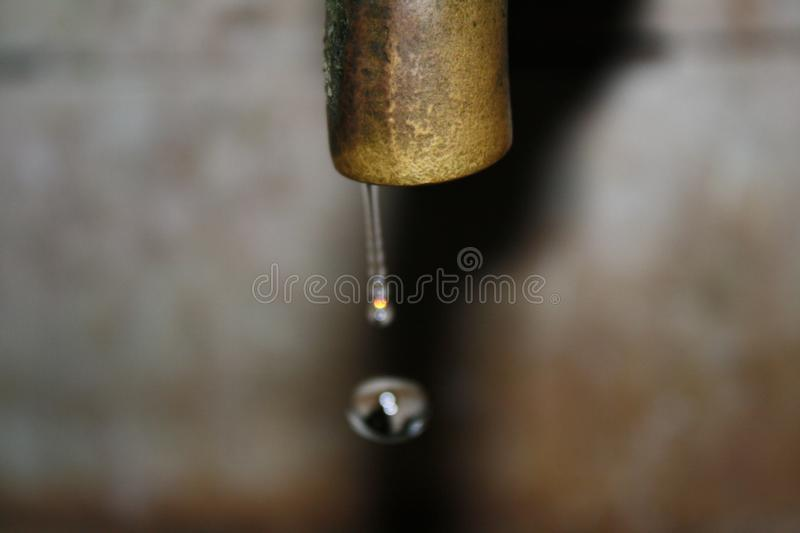 Water droplet from a metal faucet stock images