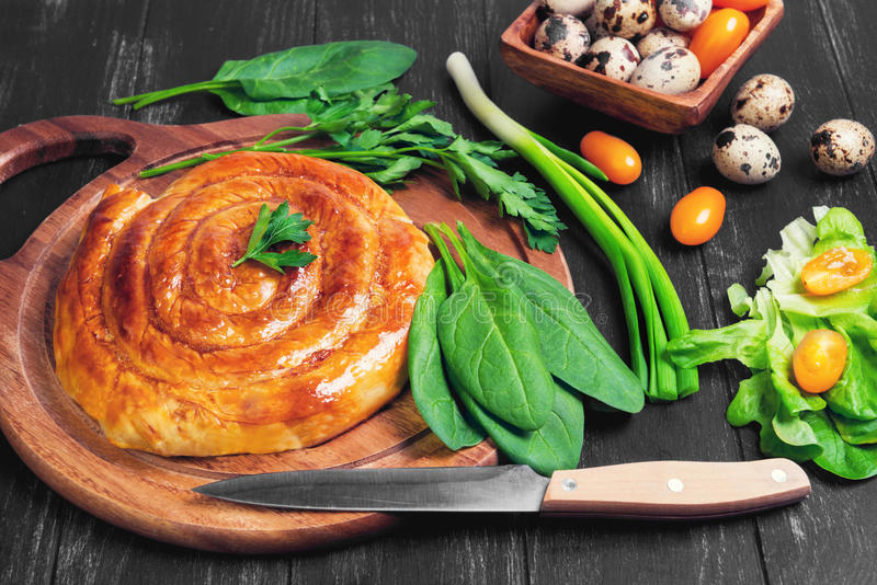 Spiral filo pie. S burek, Greek Bougatsa, lettuce, green onions, parsley, yellow cherry tomatoes, quail eggs in a wooden bowl on a napkin on a dark black stock images