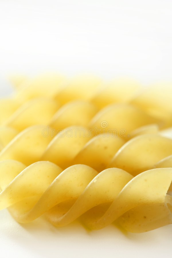 Spiral fusilli dired pasta macro over white