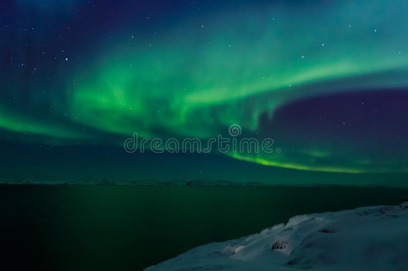 Spiral green Northern lights shining over the fjord with mountains in the background, Nuuk, Greenland stock image