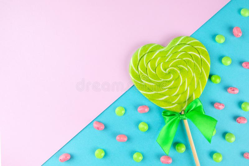 spiral heart lollipop on soft pink and blue diagonal background among small colorfull candies stock photos
