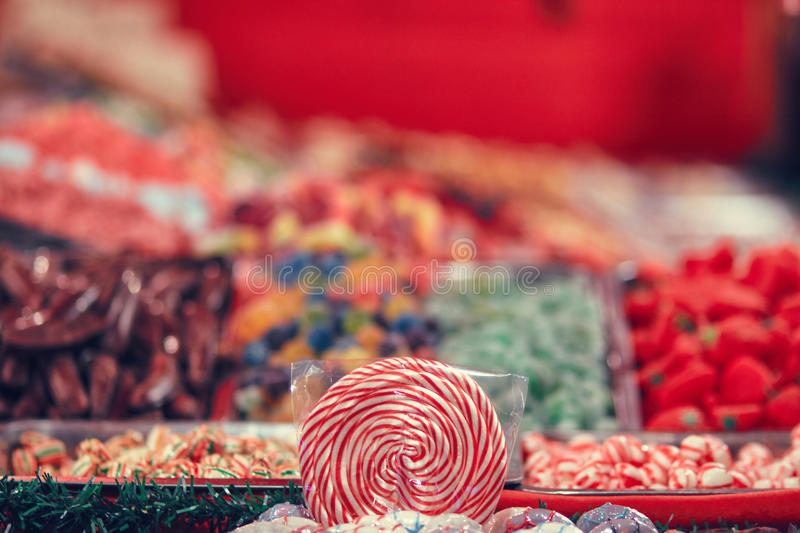 Spiral lolipop surrounded by colorful candy blur stock images