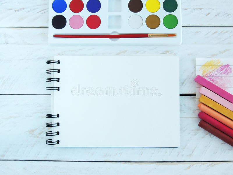 Spiral notebook with acrylic paint set and soft and oil pastels. Styled stock photography with open notebook, acrylic paint set and pastels, on a white wood royalty free stock image