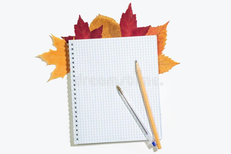 Spiral notebook in a cage with colorful autumn leaves. Pencil and pen on notepad. Isolated on white. Top view, copyspace stock photos