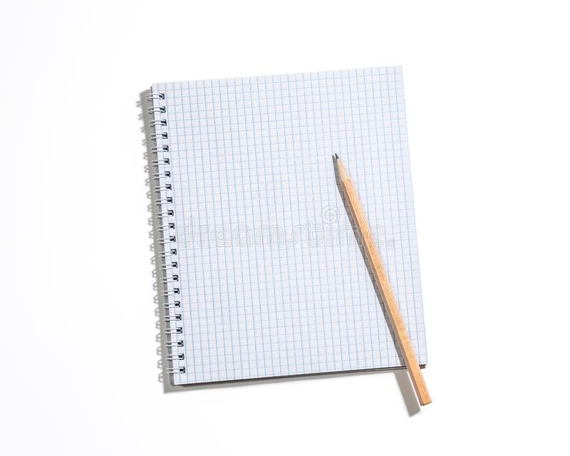 Spiral notebook in a cage with a pencil isolated on white. Top view, copyspace royalty free stock image