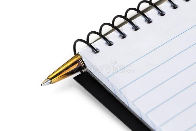 Spiral Notebook med Guld Ballpoint Pen över vit arkivfoton