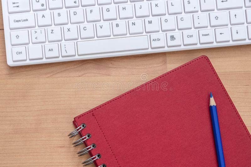 Spiral notebook with pencil and computer keyboard. On the desk royalty free stock images