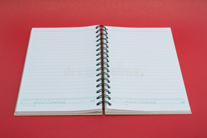 Spiral notebook on red background. royalty free stock photos