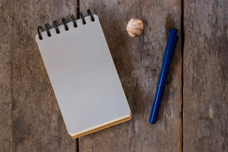 Spiral notepad blank page and pen on wooden background. Empty sketchbook top view photo. Grey paper notepad royalty free stock photo