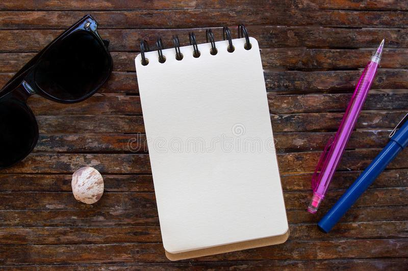 Spiral notepad blank page and pen on wooden background. Empty sketchbook top view photo. White paper notepad royalty free stock images