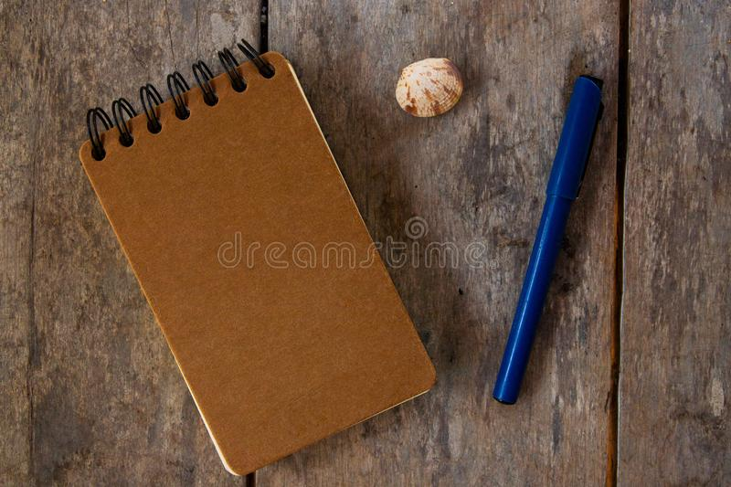 Spiral notepad craft cover and pen on wooden background. Empty sketchbook top view photo. Brown paper notepad stock images