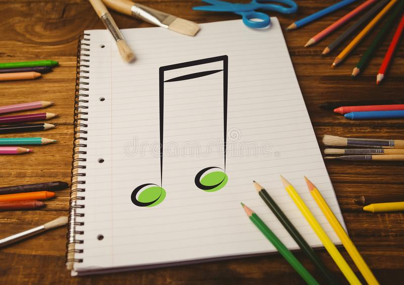 Spiral notepad with music sign and colored pencils on table. Spiral notepad with music sign and colored pencils on wooden table royalty free stock photography