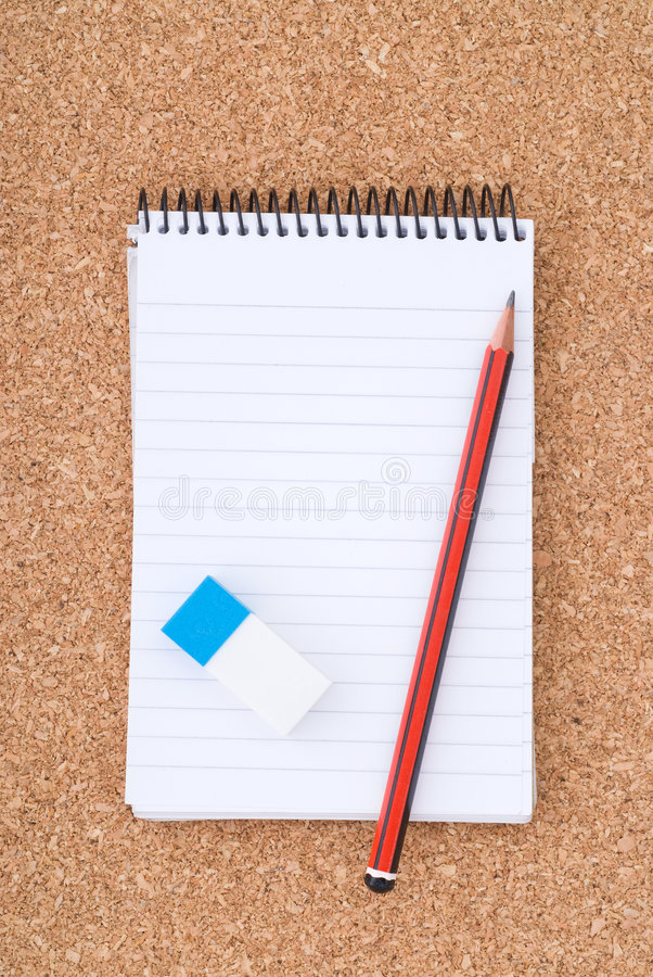 Spiral Notepad, Pencil and eraser on cork surface stock photos