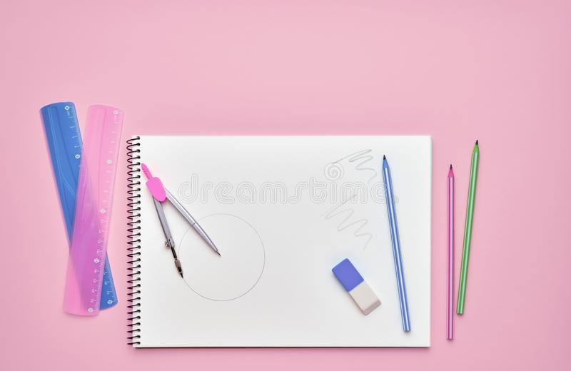 Spiral notepad with pencils. Notebook on pastel pink backdrop. Back to school concept. Copy space, top view.  royalty free stock photos