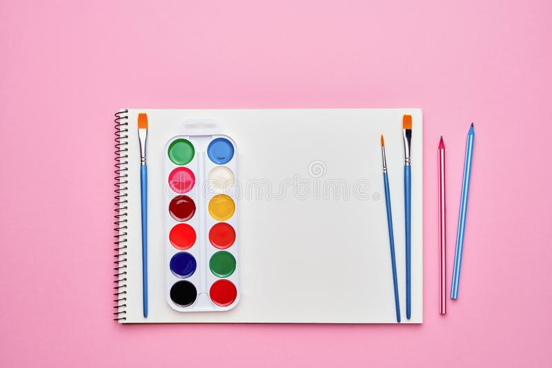 Spiral notepad with pencils. Notebook on pastel pink backdrop. Back to school concept. Copy space, top view.  stock photography
