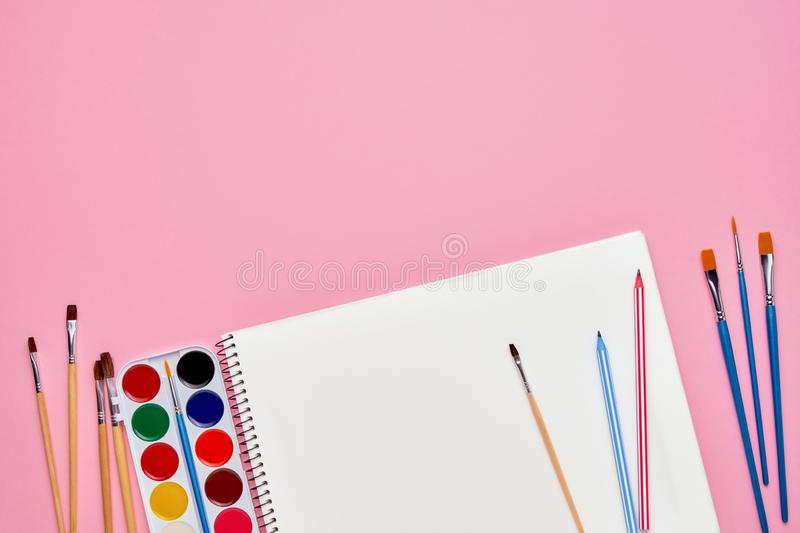Spiral notepad with pencils. Notebook on pastel pink backdrop. Back to school concept. Copy space, top view. Spiral notepad with pencil, brush and watercolors as stock photo