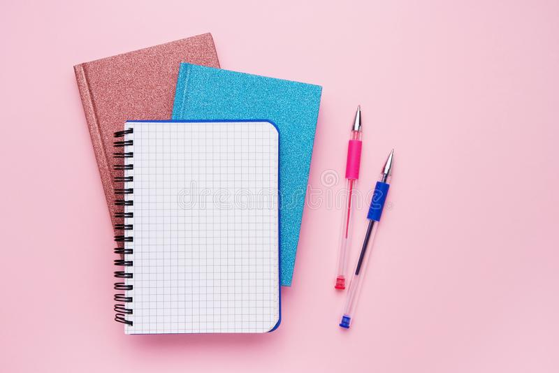 Spiral notepad with pens as mockup for your design on pastel pink backdrop. Back to school concept. Copy space, top view royalty free stock photos