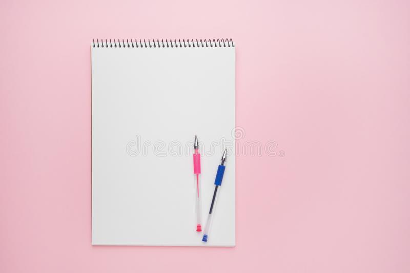 Spiral notepad with pens. Notebook on pastel pink backdrop. Back to school concept. opy space, top view stock photo