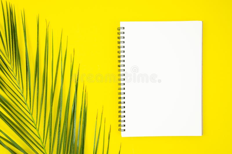 Spiral notepad with tropical palm leaf mockup on yellow background. Minimal summer concept. Frame with copy space royalty free stock images