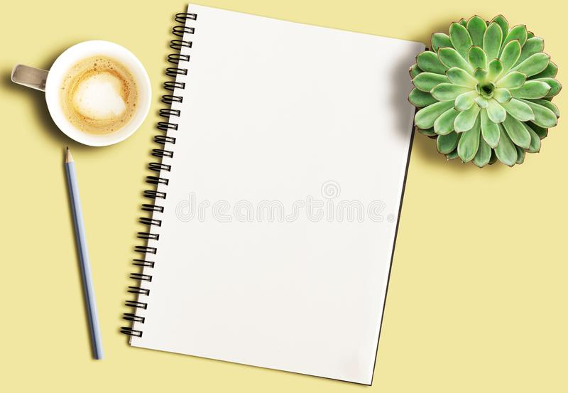 Spiral notepad on yellow desk with pencil, potted succulent plant and coffee mug stock photo