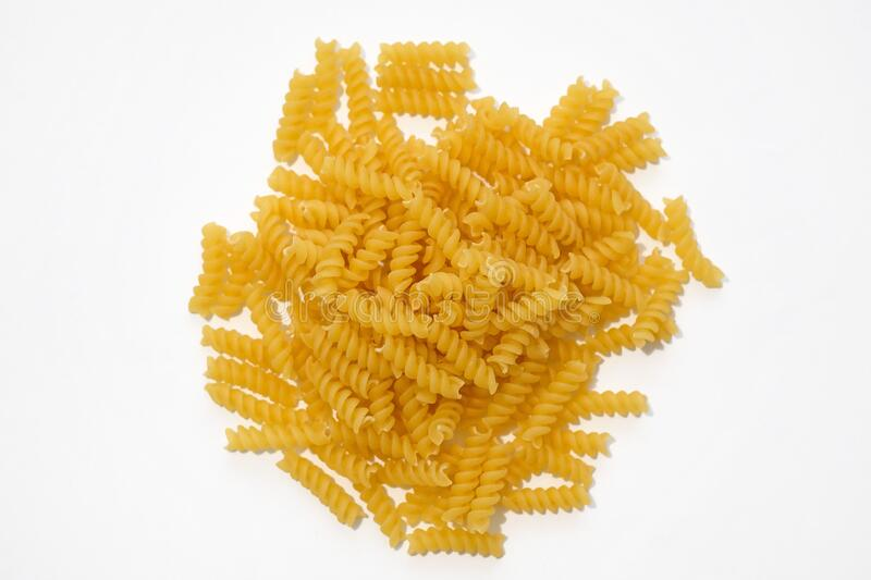 Spiral pasta on a white background. Uncooked italian pasta top view. Durum wheat pasta royalty free stock image