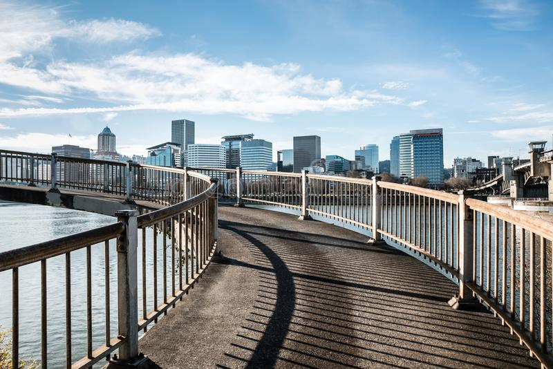 Spiral pedestrian bridge overlooking the Willamette River and the downtown city skyline in Portland, Oregon December 2017. Walking on the Eastbank Esplanade will royalty free stock image