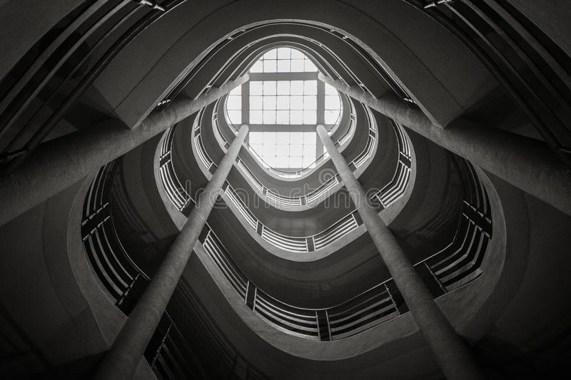 Spiral staircase climbing upward, black and white stock photo
