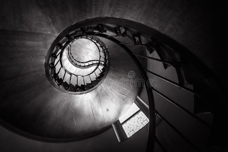 Spiral staircase in old building, bottom view of circular stair. Wooden round stairway in house interior, effect of hypnosis and. Perspective. Black and white stock photography