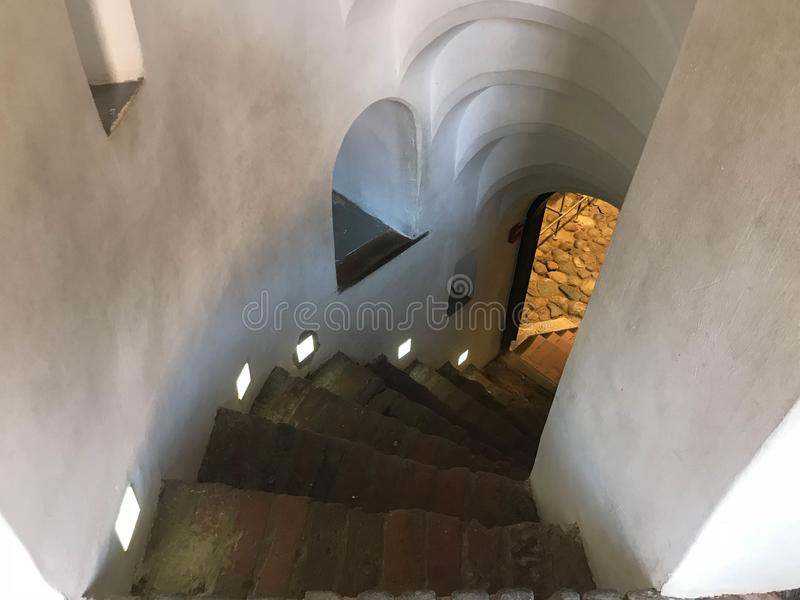 Spiral trappa för brant sten som går ner från momenten arkivbilder
