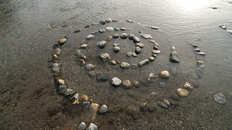 Spirale von Kiesel zu Steine, auf dem Ufer, Strand Gravedona im See Como lizenzfreie stockfotos