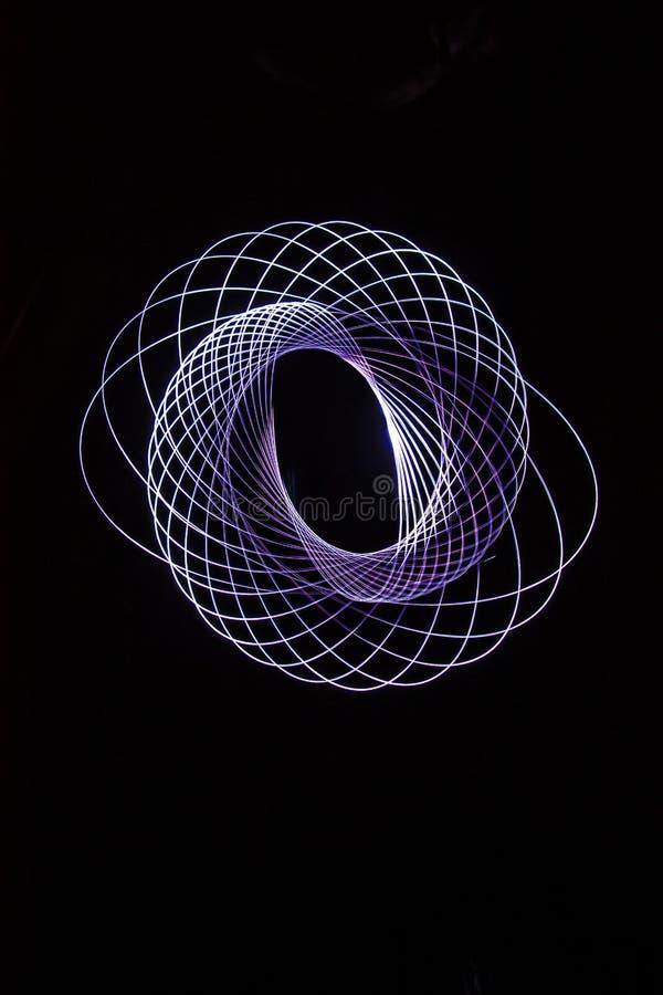 Spiralen, door een klein licht dat in dark worden getrokken stock afbeelding