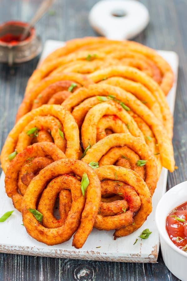 Spiralen van de aardappel en de kaas in olie stock afbeeldingen