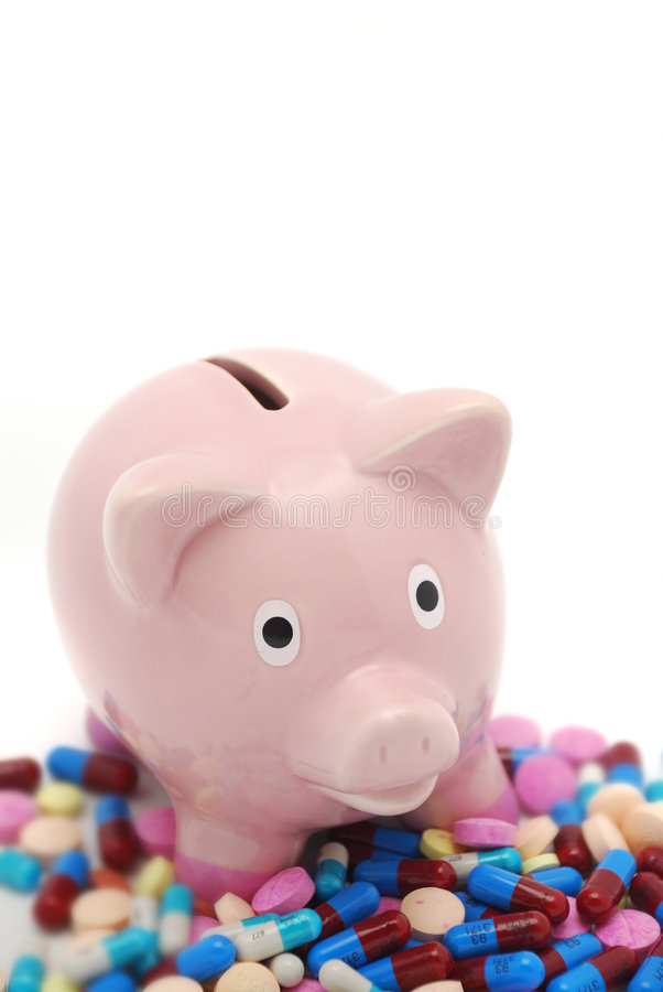 Spiraling health care costs. Piggy bank surrounded by pills over white background stock photography