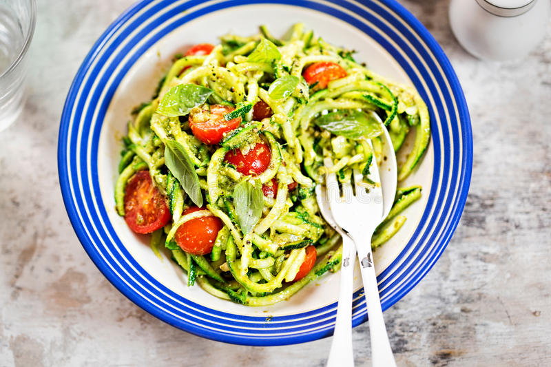 Spiralled courgette with green pesto and cherry tomatoes royalty free stock photos