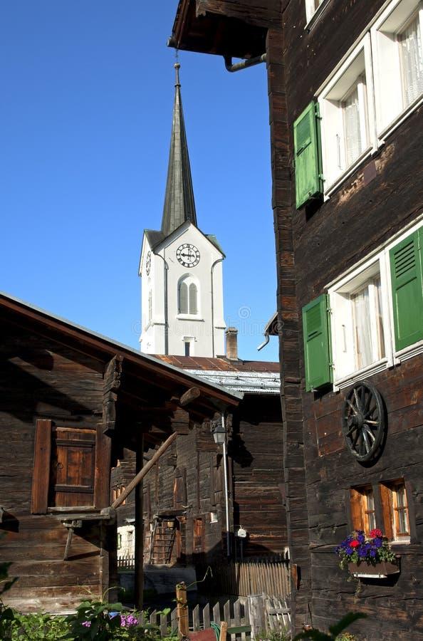 Spire behind Swiss chalets. Ulrichen , Obergoms, Valais, Switzerland stock photo