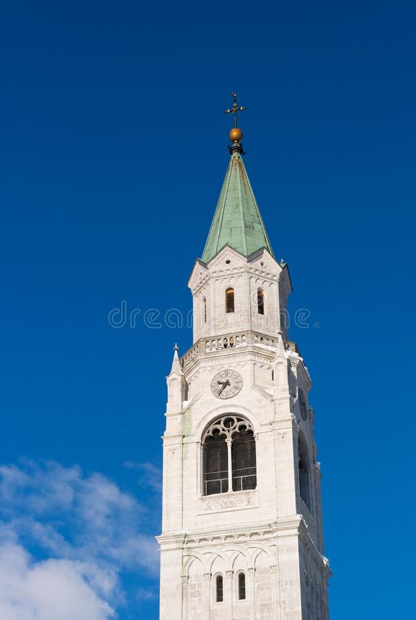 The Spire of the Catholic Parish Church in Cortina d` Ampezzo. Bell Tower of the Catholic Parish Church in Cortina d` Ampezzo, called Basilica Minore dei Santi royalty free stock images