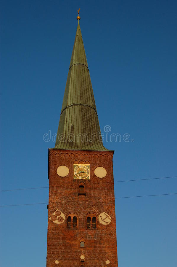 Spire on tower of Aarhus Cathedral. The copper spire of Aarhus Dome church against a deep blue evening sky royalty free stock image