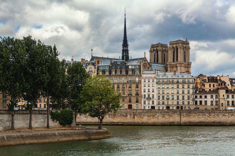 Spire and towers of Notre-Dame cathedral among parisian buildings stock images