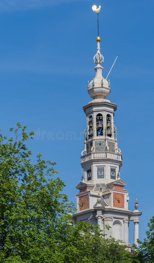 Spire of the Zuiderkerk in Amsterdam. Amsterdam, the Netherlands - August 16, 2016: The spire of the Zuiderkerk against blue sky with green tree in lower left royalty free stock photo