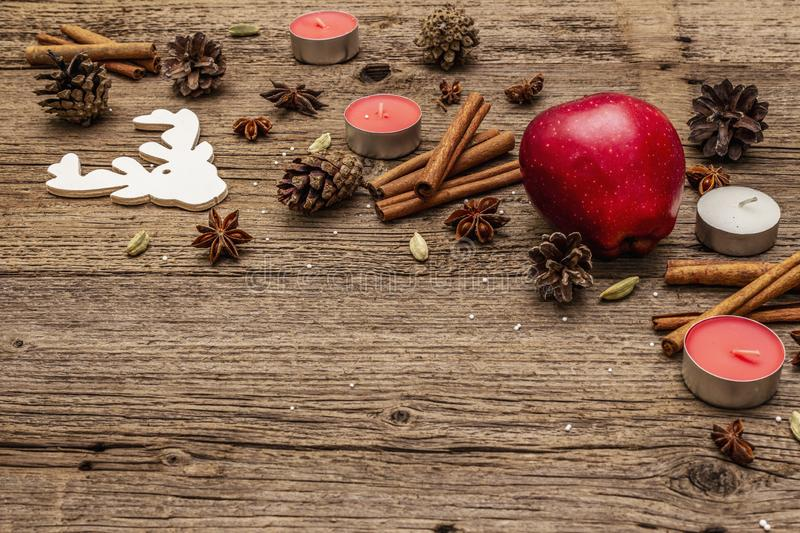 Spirit Christmas background. Apple, candles, spices, deer, cones. Nature New Year decorations, vintage wooden boards. Copy space royalty free stock photography