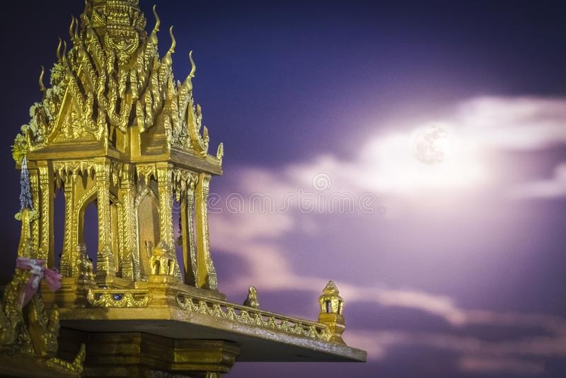 Spirit house in thailand with garland and some wreathes during the super moon stock image