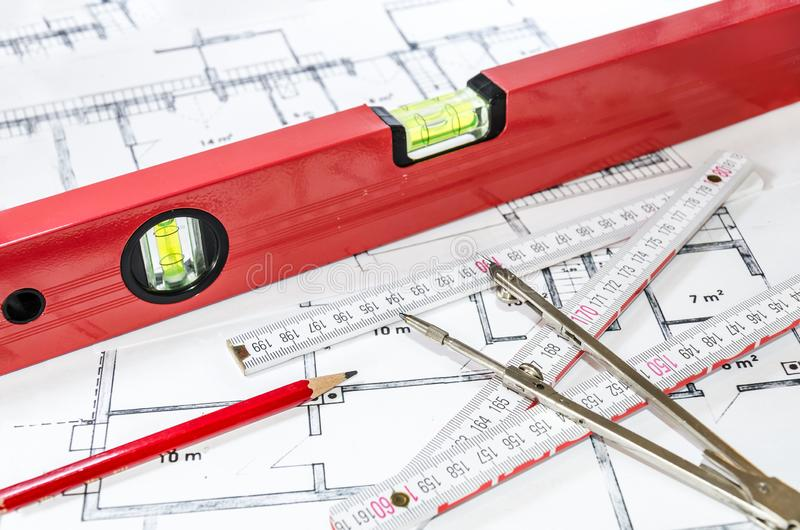 Spirit level and other measurement equipment lying on generic building plan stock image