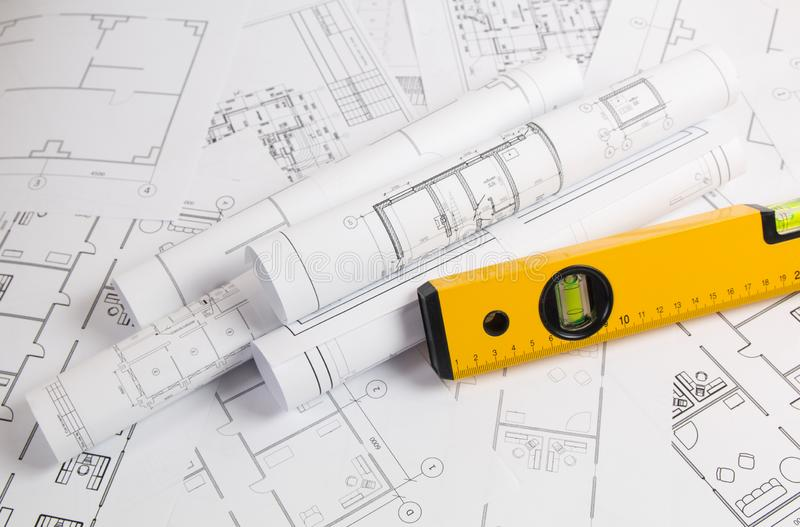 Spirit level and paper еngineering house drawings and blueprints. Yellow spirit level and paper engineering house drawings and blueprints royalty free stock photo