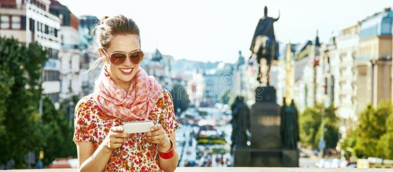 Traveller woman on Vaclavske namesti in Prague writing sms. The spirit of old Europe in Prague. happy modern traveller woman on Vaclavske namesti in Prague stock image