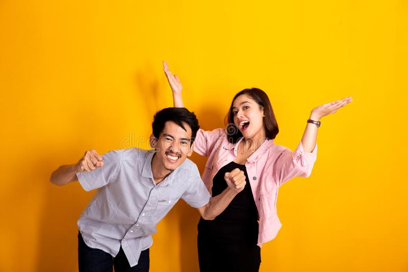 Spirit of young asian couple. Over yellow background stock photo