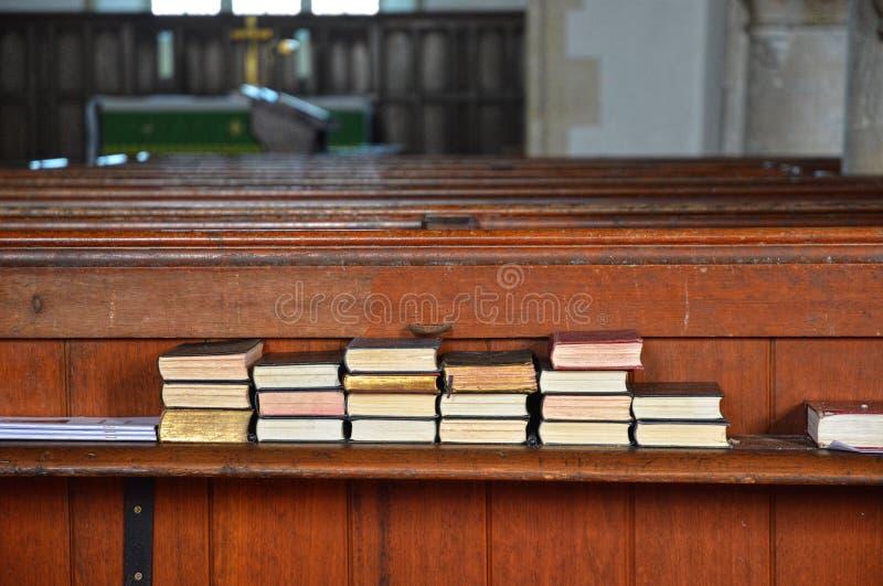 Spiritoso elevando i libri di inni religiosi impilati sul banco di chiesa immagini stock libere da diritti
