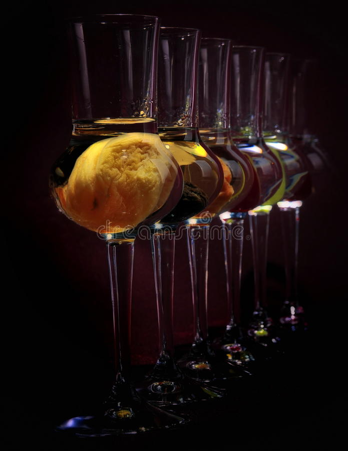 Spirits within. A line of spirits, strong drinks made from different fruits in tall glasses stock images
