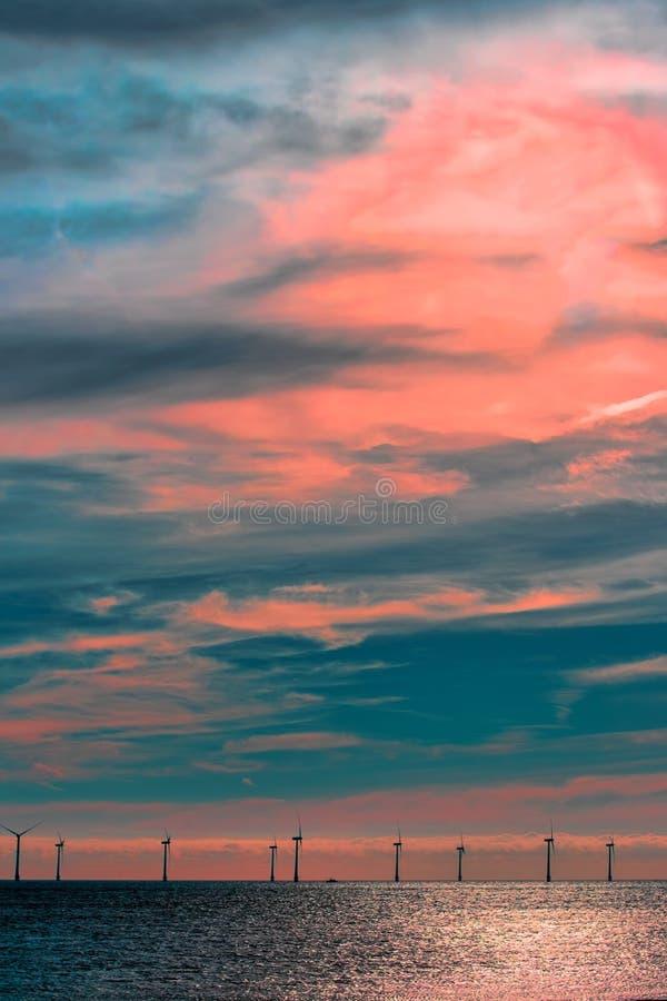 Spiritual awakening, Offshore wind farm cloudscape. Turbines under pink sunset sky stock image